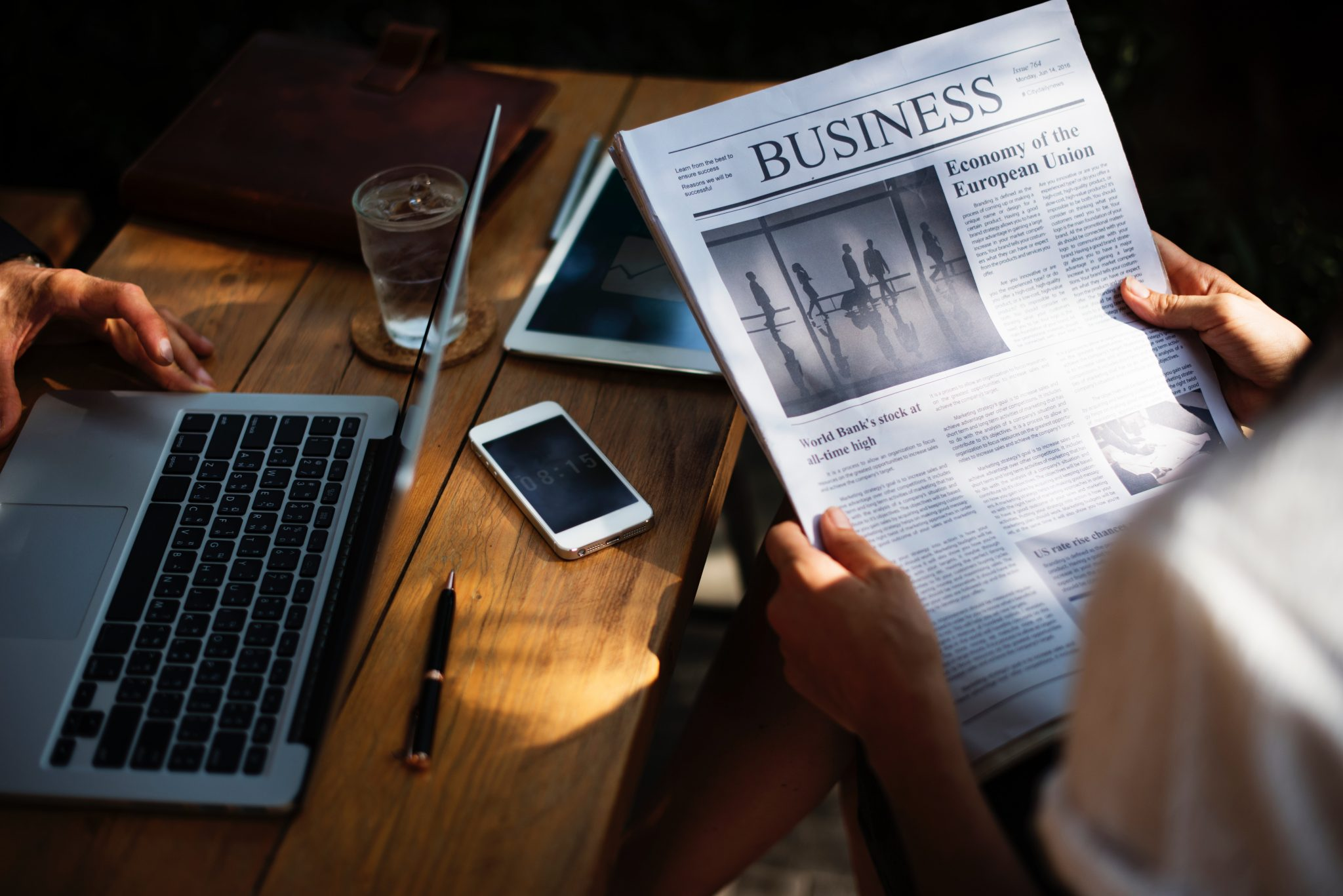 One person reads the business newspaper while another uses a laptop - Baldwin Financial Services - Seaton Financial Advisers