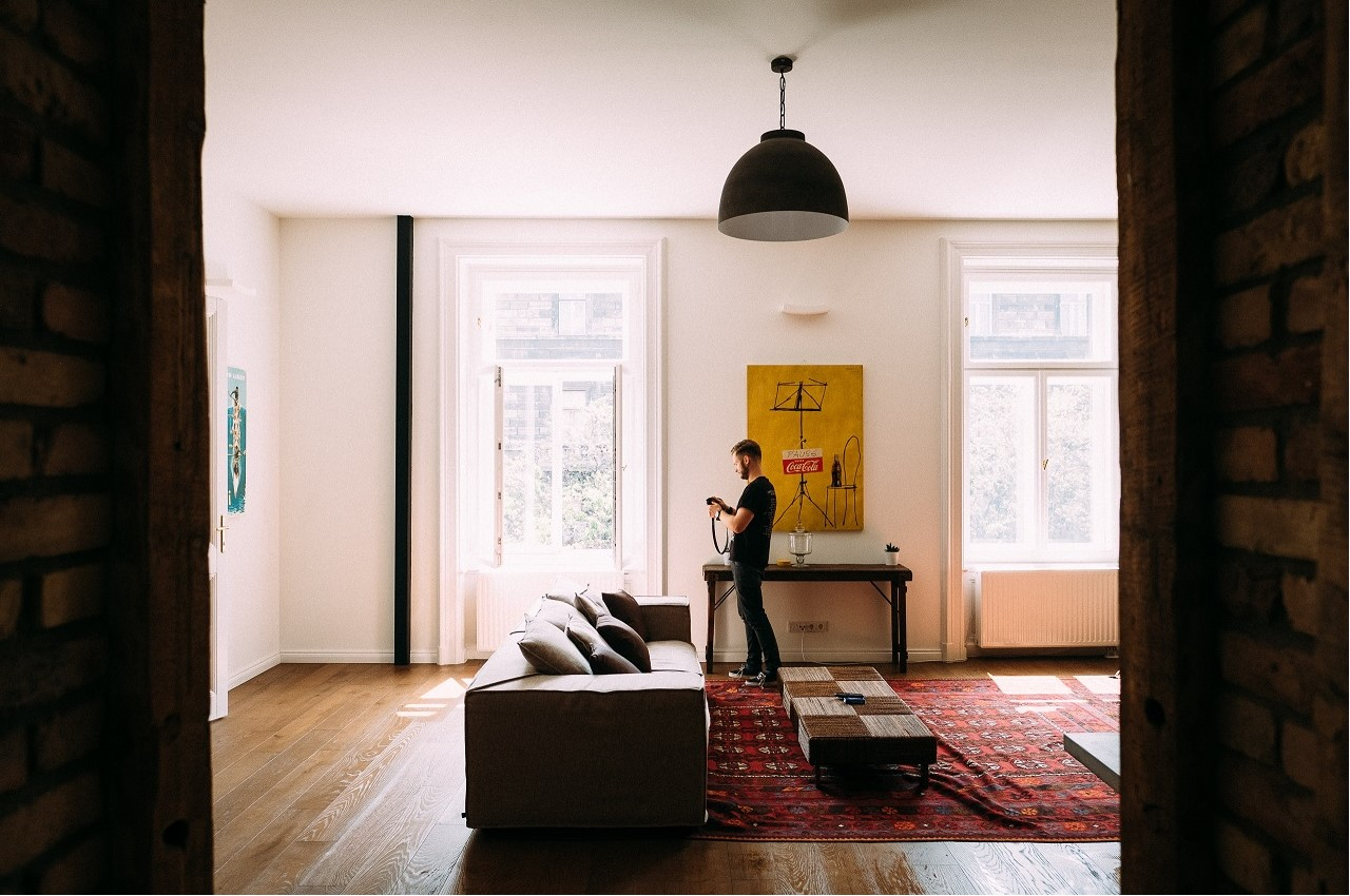 A young man in a spacious, well-lit lounge - First Home Super Saver Scheme