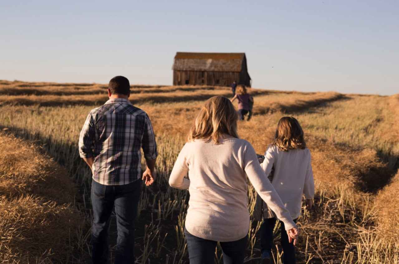 A family walking through a golden field, headed towards an isolated barn - Total and Permanent Disability Insurance