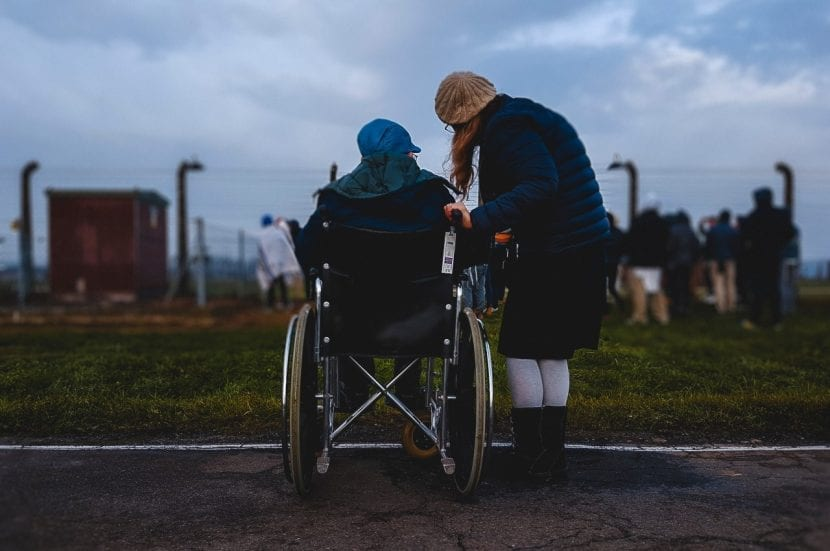 A lady outside in a wheelchair, with her friend, looking towards a crowd of people all watching something happening in a field - Trauma Insurance