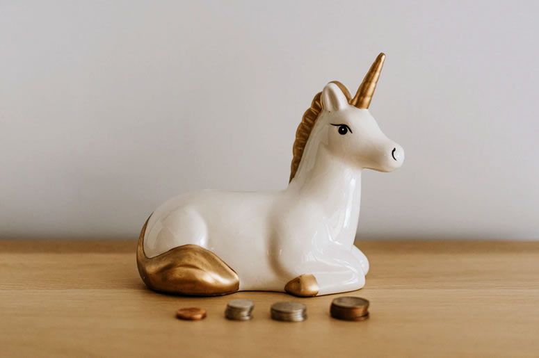 White and gold ceramic money box in the shape of a unicorn, with four small piles of coins stacked up in front: Protecting Your Super