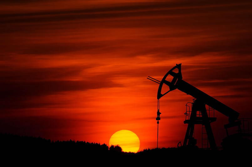 A stunning red sky and setting sun behind the silhouette of oilfield machinery.