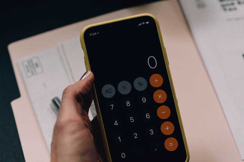 Key Superannuation Rates & Thresholds: A person using a calculator app on their smartphone, with paperwork on the table in the background.