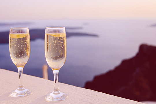 Two glasses of bubbling champagne on a ledge, in the evening sun, with sea views in the background.